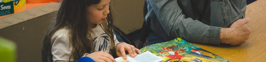 child reading to adult volunteer