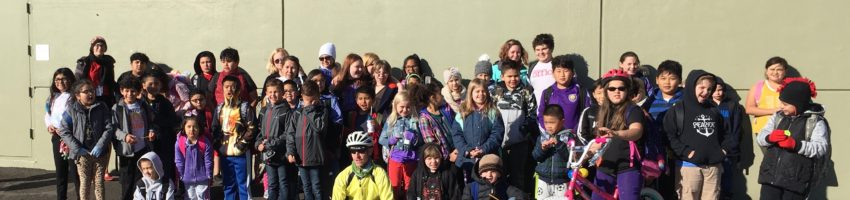 students who walked and biked to school smiling outside the building