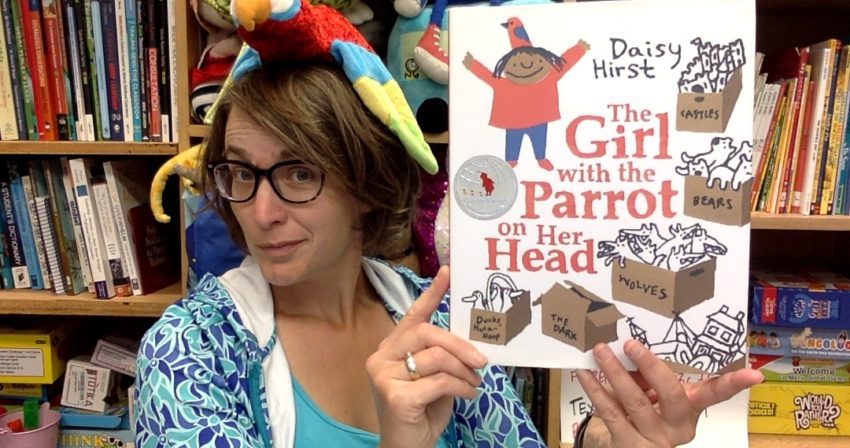 Ms. Snyder holds up the book, The Girl with the Parrot on Her Head. Both the girl in the illustration on the book and Ms. Snyder have a parrot on her head.