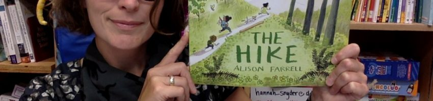 Ms. Snyder smiles as she holds up a copy of the book _The Hike_. The cover shows three kids and a dog running up a forested trail.