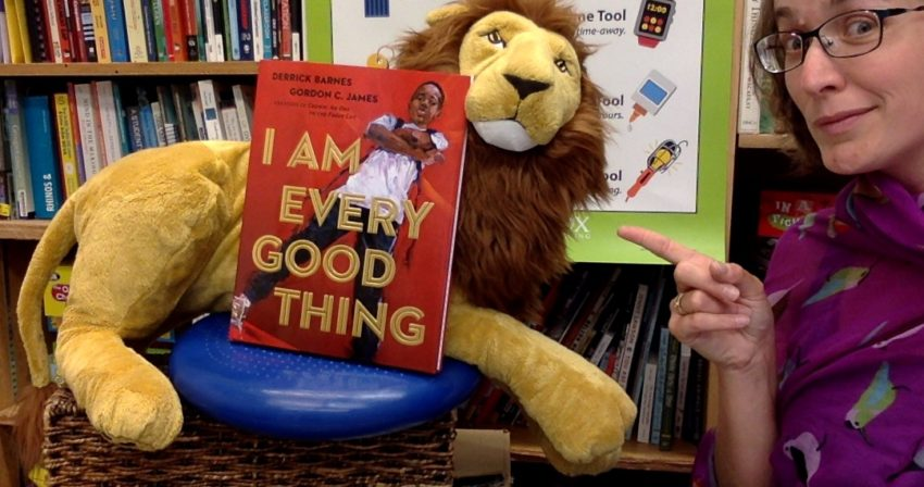 Ms. Snyder points to a large stuffed lion holding up a copy of the book, _I Am Every Good Thing_