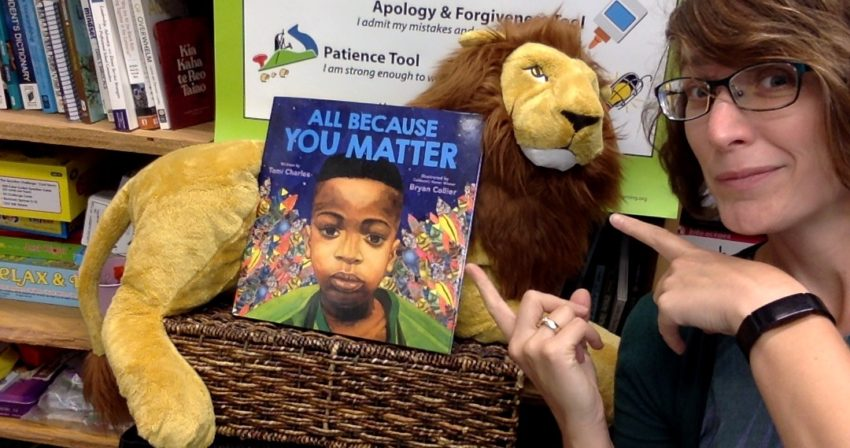 Ms. Snyder points to a stuffed lion holding up a copy of the book: All Because You Matter