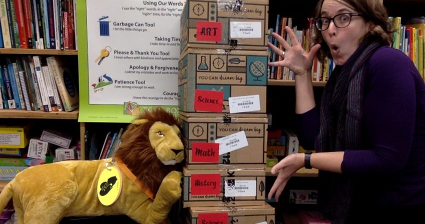 Ms. Snyder and Leo the Lion show off a stack of 4th grade supply boxes.