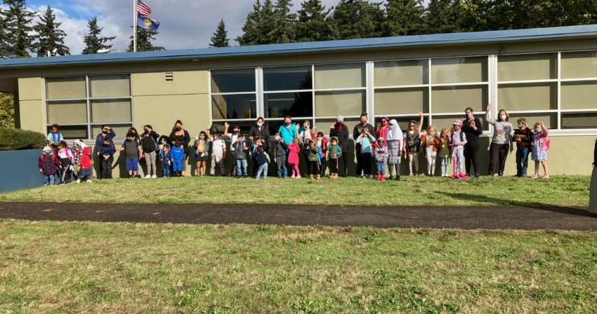 Participants in the 10/6/21 Walk & Roll to school day stand in front of the school, waving